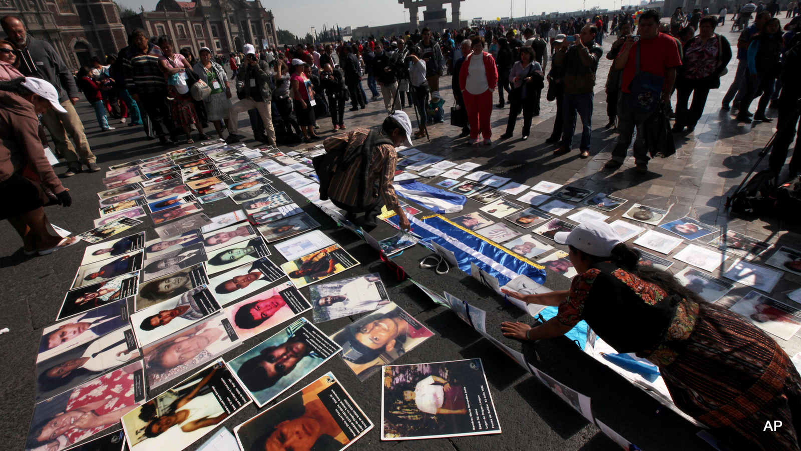 Central American mothers lay pictures of their children who went missing while crossing Mexico for the United States, on the steps of the Basilica de Guadalupe in Mexico City, Saturday Nov. 29, 2014.