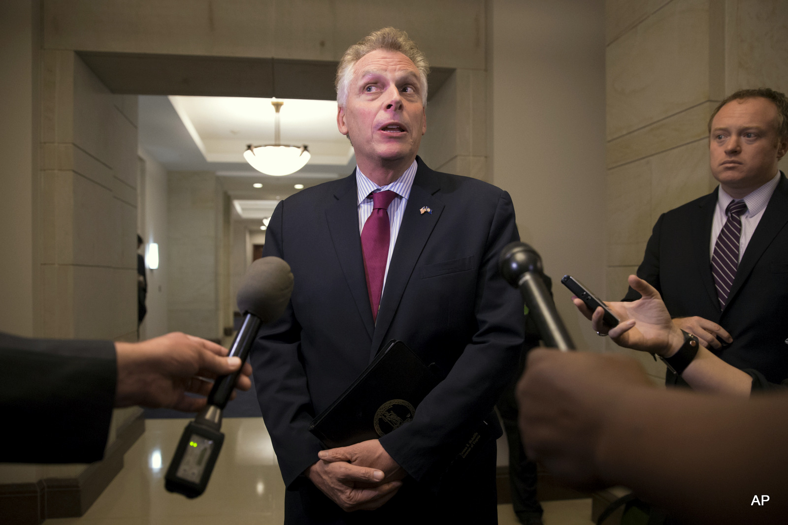 Virginia Gov. Terry McAuliffe speaks with reporters on Capitol Hill in Washington.  McAuliffe helped fund the failed state Senate campaign of the FBI official's wife who later go on to clear investigate Hillary Clinton's use of a private email server.
