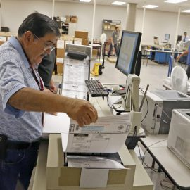 An Arizona elections official at the Maricopa inserts ballots into a machine to recount the votes in the 5th Congressional District race Tuesday, Sept. 13, 2016, in Phoenix. (AP Photo/Ross D. Franklin)