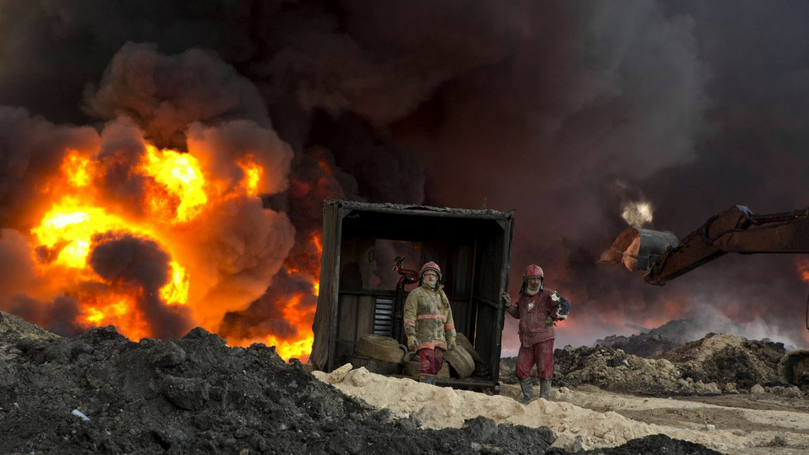 Iraqi fire fighters work to quell a dangerous oil fire set by ISIS militants in Qayara, south of Mosul, Iraq, Monday, Nov. 28, 2016. (AP Photo/Maya Alleruzzo)