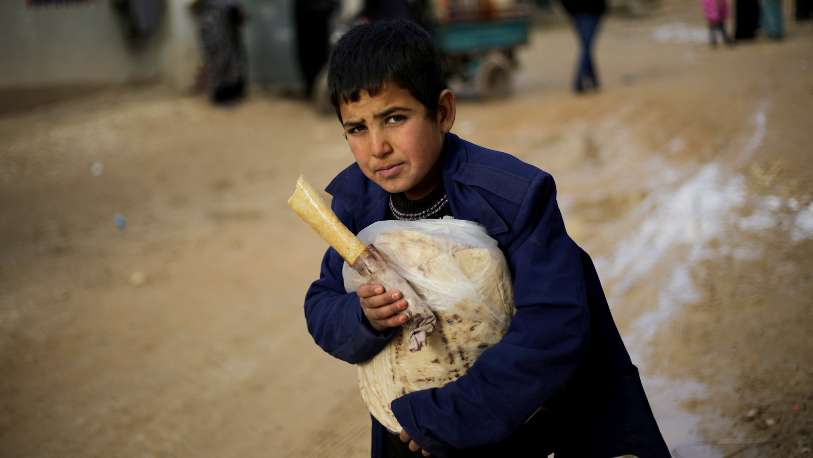 A Syrian boy displaced with his family from eastern Aleppo holds a sandwich and bread bag in the village of Jibreen south of Aleppo, Syria, Saturday, Dec. 3, 2016. (AP Photo/Hassan Ammar)
