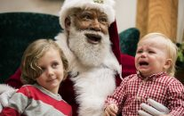 In this Thursday, Dec. 1, 2016 photo, Larry Jefferson, playing the role of Santa, smiles with Auden Good and his one-year-old brother Ezra of Ramsey while posing for photos at the Santa Experience at Mall of America in Bloomington, Minn. (Leila Navidi/Star Tribune via AP)