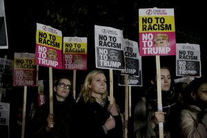 People hold placards as they take part in an anti-racism protest against President-elect Donald Trump winning the American election, outside the U.S. embassy in London, Wednesday, Nov. 9, 2016. (AP/Matt Dunham)