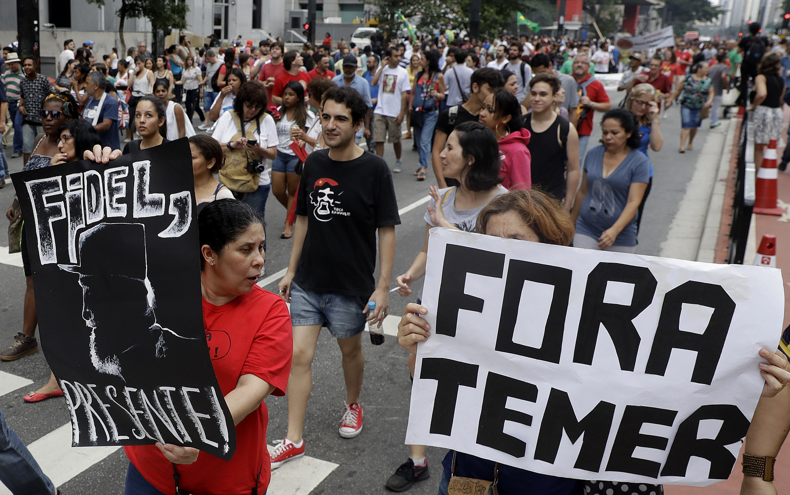 "Demonstrators march with a sign that says in Portuguese ""Get out Temer"" and a drawing of Cuba's late President Fidel Castro, as they demand the impeachment of Brazil's President Michel Temer in Sao Paulo, Brazil, Nov. 27, 2016. (AP/Andre Penner)"