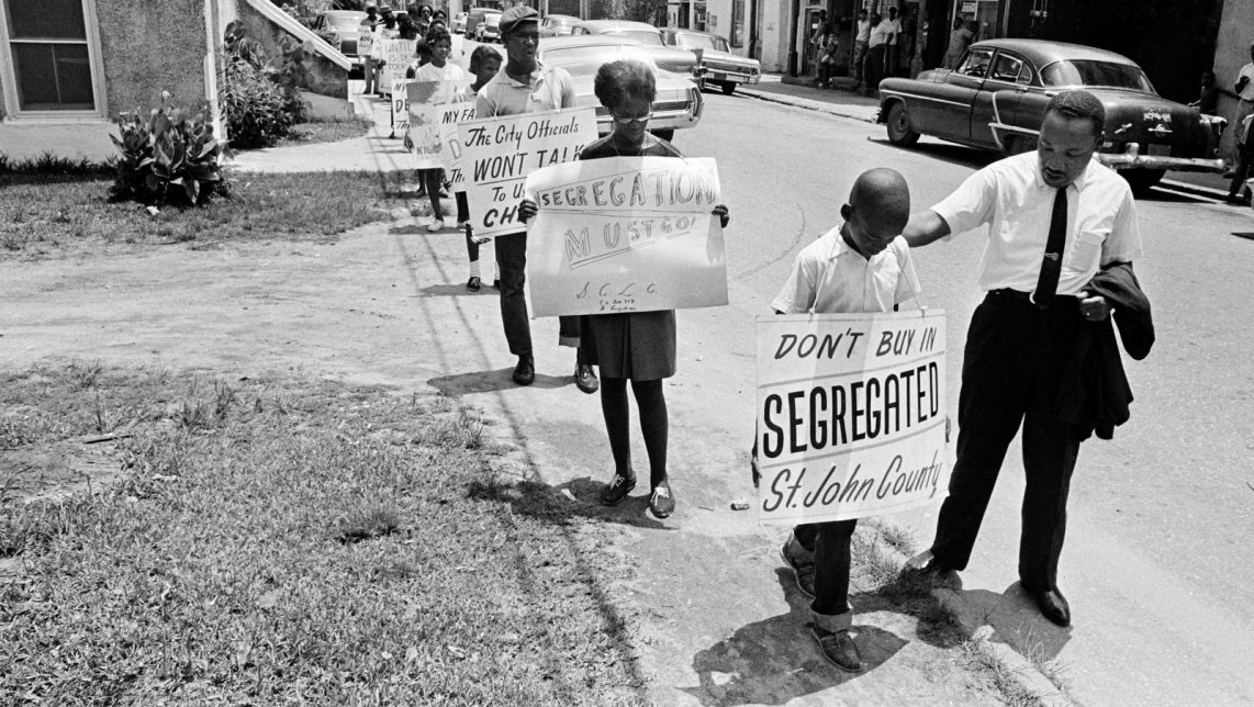 Dr. Martin Luther King, Jr. gives a young picket a pat on the back as a group of youngsters started to picket St. Augustine, Fla., June 10, 1964. (AP Photo)