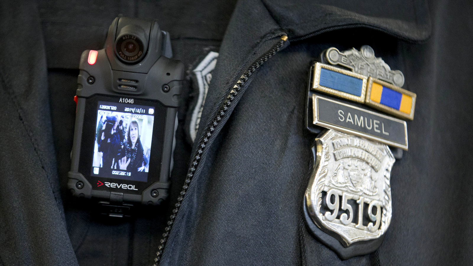 A Philadelphia police officer demonstrates a body-worn camera used as part of a pilot project in Philadelphia.  (AP/Matt Rourke)