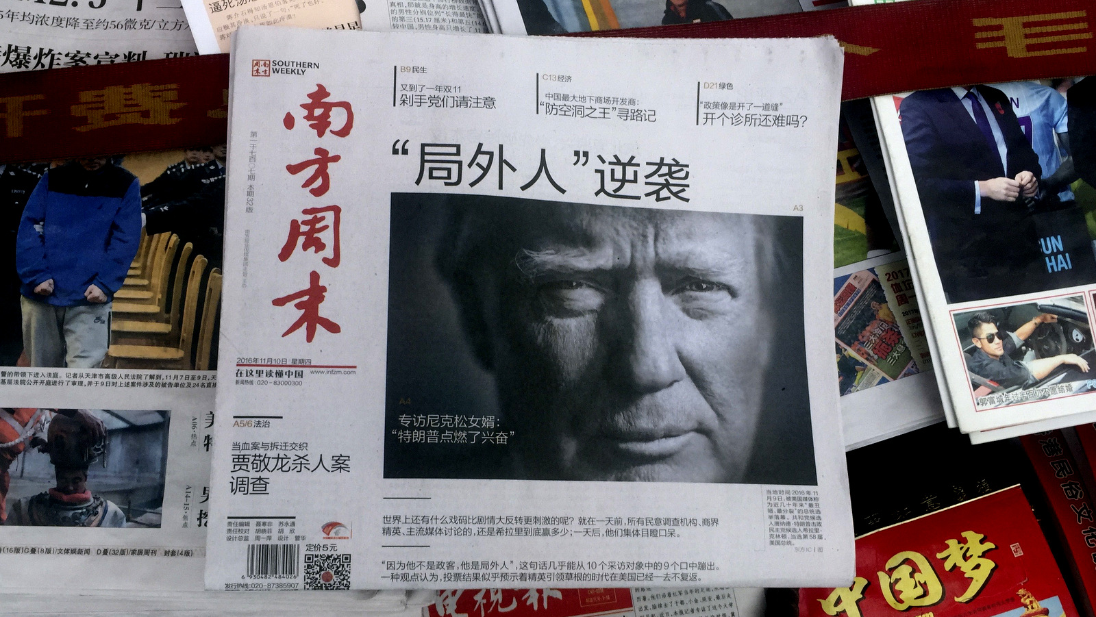 "A front page of a Chinese newspaper with a photo of U.S. President-elect Donald Trump and the headline ""Outsider counter attack"" is displayed at a newsstand in Beijing, (AP/Ng Han Guan)"
