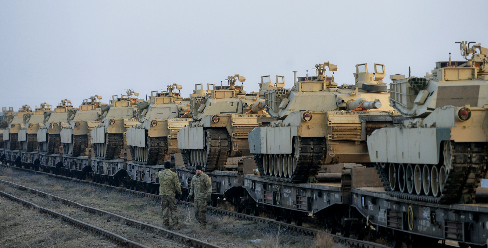 "Servicemen of the ""Fighting Eagles"" 1st Battalion, 8th Infantry Regiment, walk by tanks that arrived via train to the US base in Mihail Kogalniceanu, eastern Romania, Tuesday, Feb. 14, 2017. (AP/Andreea Alexandru)"