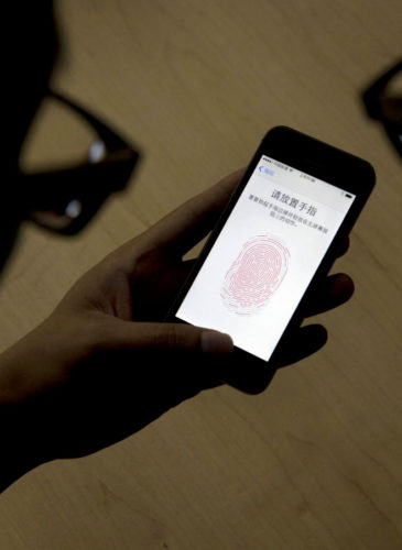 An Apple employee instructs a journalist on the use of the fingerprint scanner technology built into the company's iPhone 5S during a media event in Beijing. Watchdog groups are concerned that U.S. Customs and Border Protection agents are searching the phones and other digital devices of international travelers at border checkpoints in U.S. airports. (AP/Ng Han Guan)