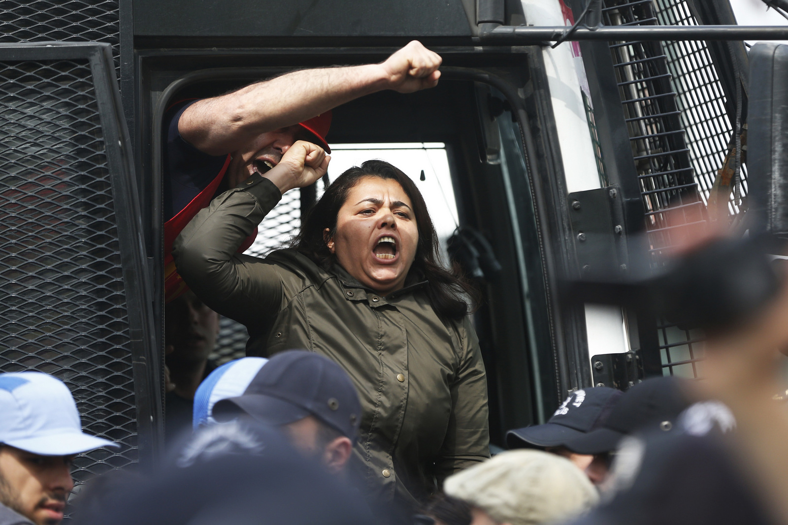 Detained protesters chant a slogan from inside a police in Istanbul, Monday, May 1, 2017. Police in Istanbul detained more than 70 people who tried to march to iconic Taksim Square in defiance of a ban on holding May Day events there. Workers and activists marked May Day with defiant rallies and marches for better pay and working conditions Monday.