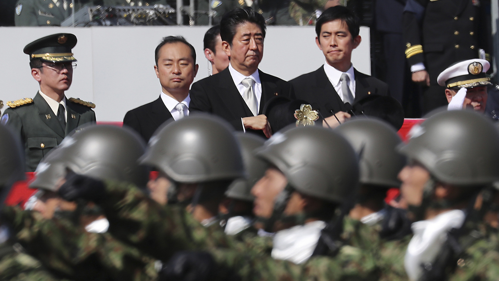 Japanese Prime Minister Shinzo Abe, center, reviews members of Japan Self-Defense Forces during a parade of the Self-Defense Forces Day at Asaka Base in Asaka, north of Tokyo. (AP/Eugene Hoshiko)