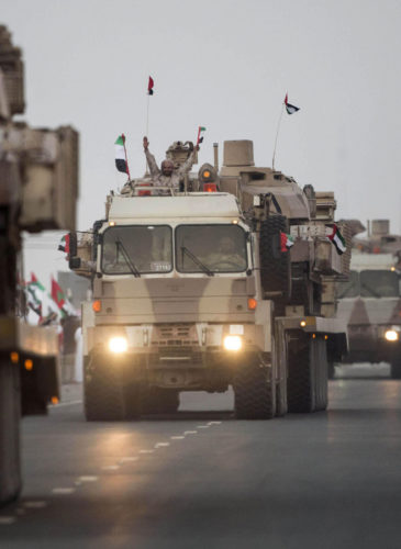 A convoy of UAE military vehicles and personnel travels from Al Hamra Military Base to Zayed Military City, marking the return of the first batch of UAE Armed Forces military personnel from Yemen, in Abu Dhabi, United Arab Emirates. (WAM via AP)