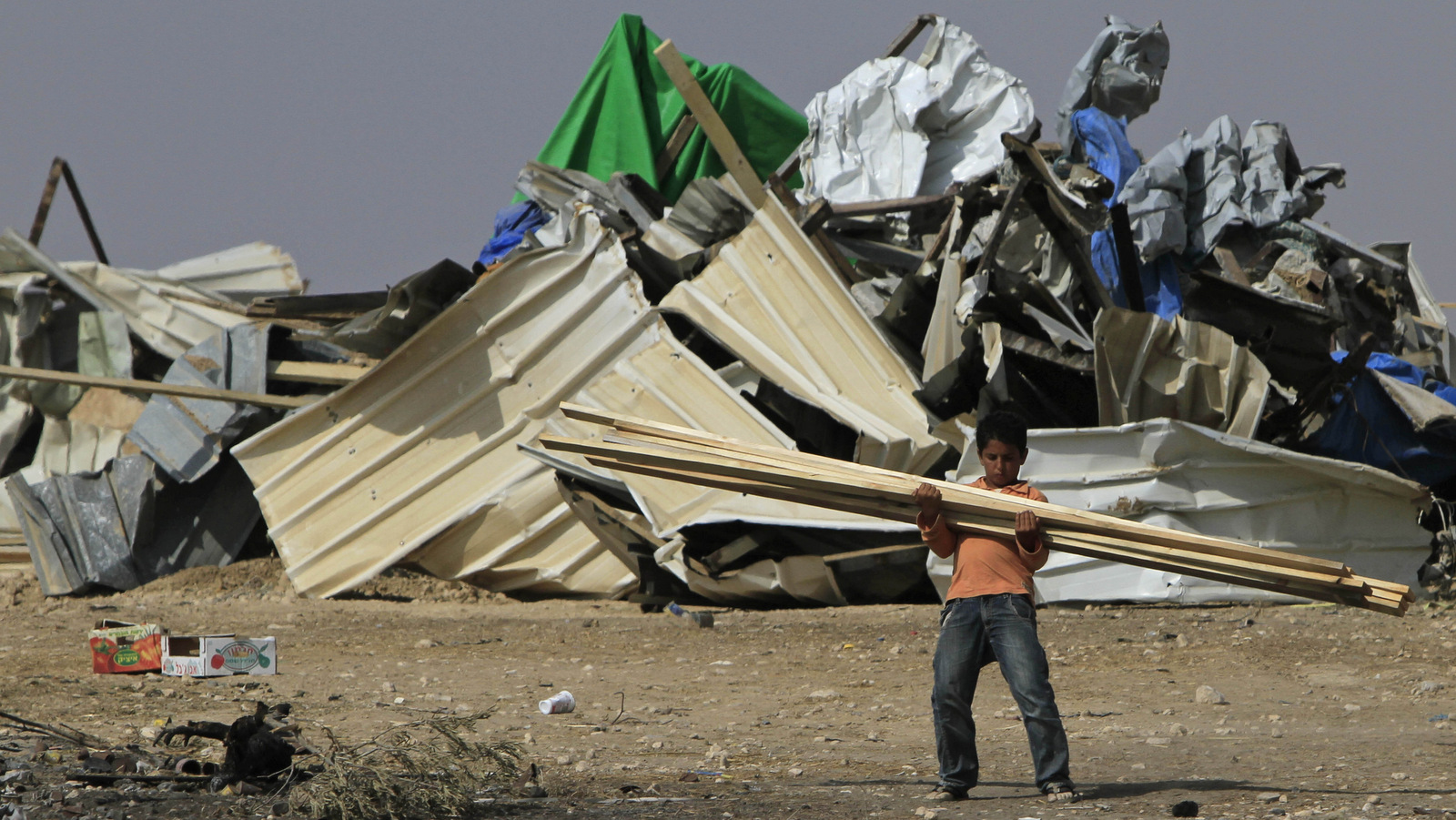 A Bedouin boy carries timber after demolished his home in the village of El Araqib near the southern Israeli city of Beersheba in 2010. (AP/Tsafrir Abayov)