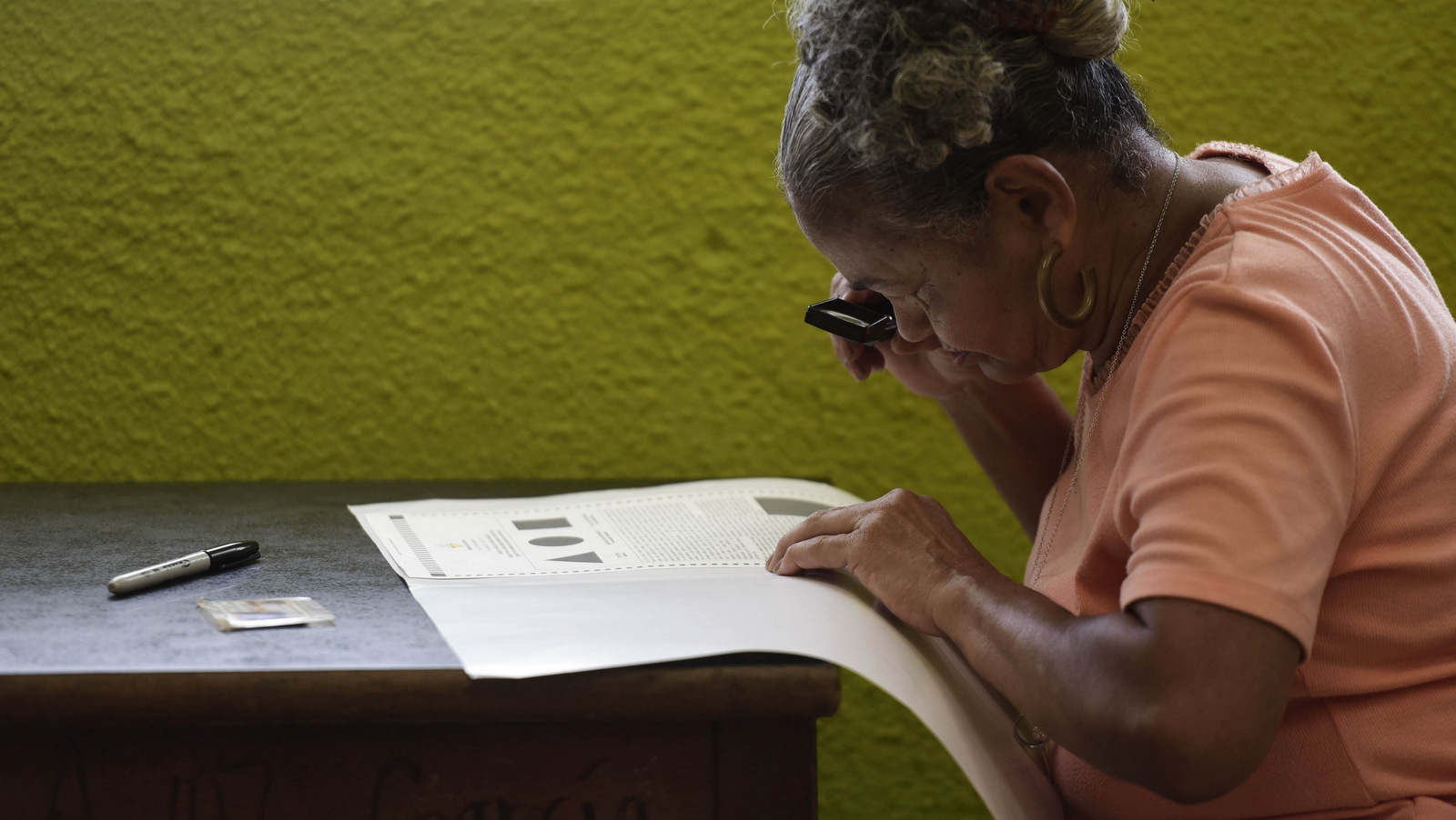 Puerto Rican resident Maria Quinones looks carefully at her ballot with a magnifying glass before voting during the fifth referendum on the island's status, in San Juan, Puerto Rico, June 11, 2017. (AP/Carlos Giusti)