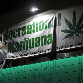 Bryce Tallitsch hangs up a sign for recreational marijuana at the NuLeaf dispensary, June 30, 2017, in Las Vegas. Nevada dispensaries were legally allowed to sell recreational marijuana starting at 12:01 a.m. Saturday. (AP/John Locher)
