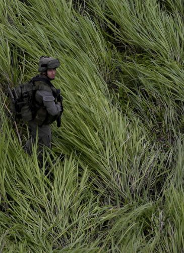 An anti-narcotics police officer stands guard at a landing zone near a cocaine lab in Calamar, Guaviare state, Colombia. Police seized cocaine and chemicals at the lab. About 104 labs have been destroyed by the police in a five day period.(AP/Fernando Vergara)