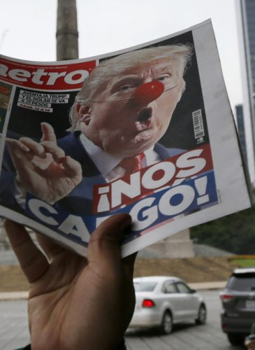 "A street vendor hawks a newspaper emblazoned with an image of Donald Trump with a clown's nose, and a headline that reads in Spanish: ""We're screwed!,"" in front of the Angel of Independence monument, in Mexico City, Wednesday, Nov. 9, 2016. (AP Photo/Marco Ugarte)"