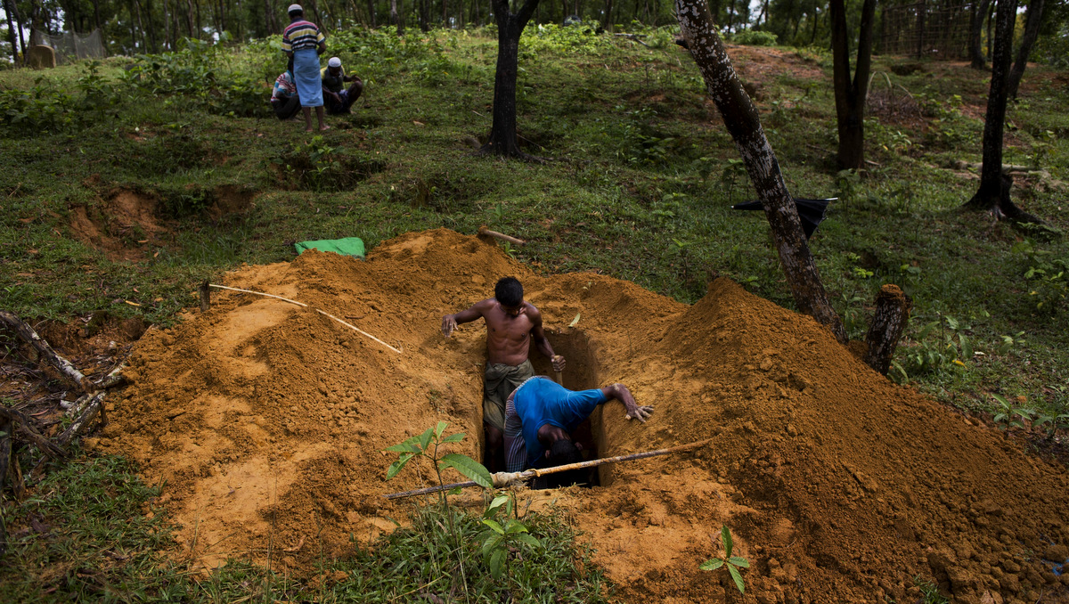 Rohingya men dig a grave in Kutupalong's refugee camp's cemetery, Bangladesh, Sept. 8, 2017. This massive refugee camp was set up in the early 90s to accommodate the first waves of Rohingya Muslim refugees who started escaping convulsions of violence and persecution in Myanmar. (AP/Bernat Armangue)
