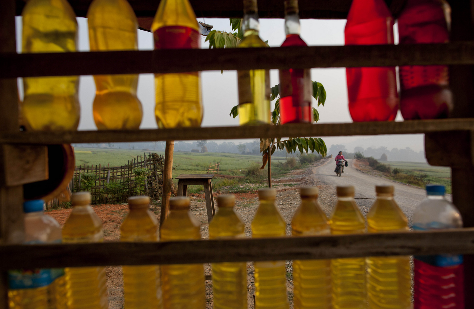 Gasoline filled in to plastic bottles are on display at a roadside shop in Mong Pan, Northern Shan estate, Myanmar. Myanmar put over 20 offshore oil and gas exploration blocks up for auction as the country pushed to attract foreign investment. (AP/Gemunu Amarasinghe)