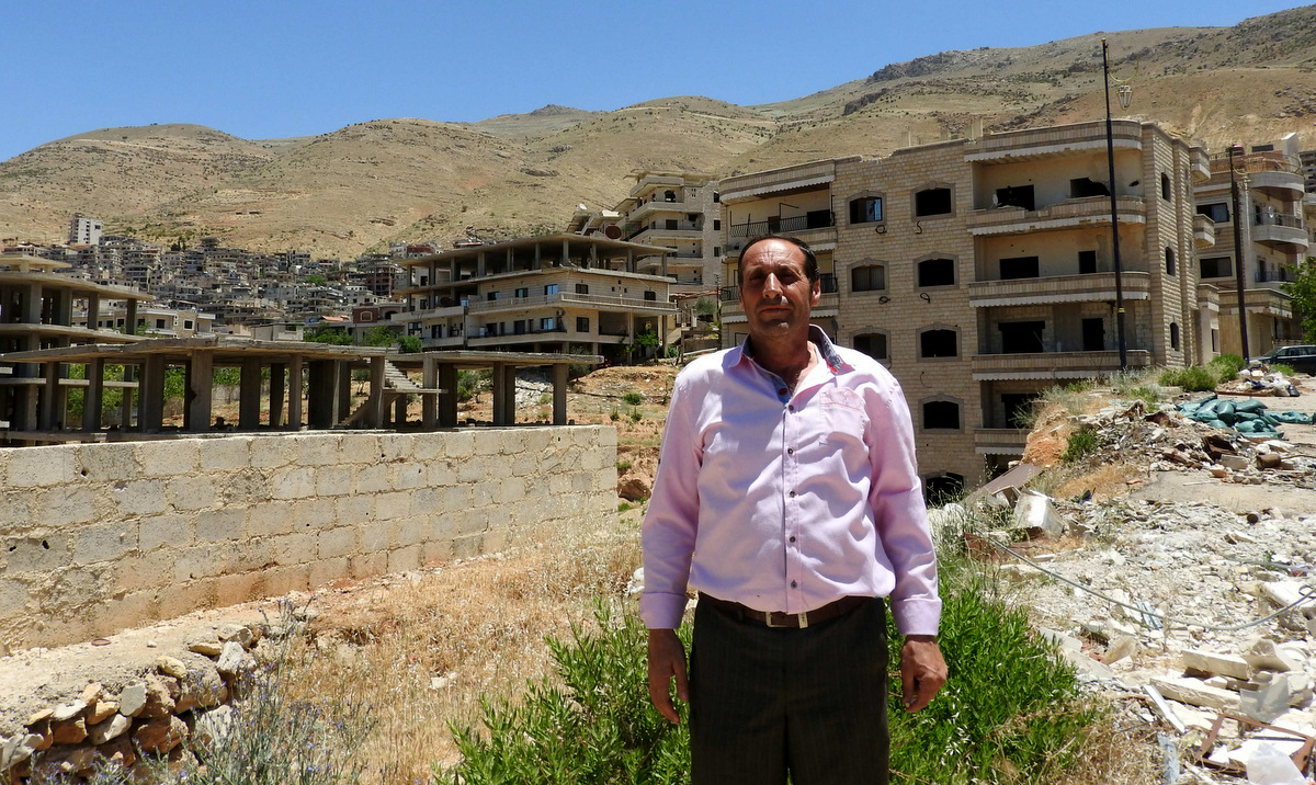 "The Mayor of Madaya, standing near buildings once occupied by ""moderate rebels"" who sniped and fired mortars on the road below."