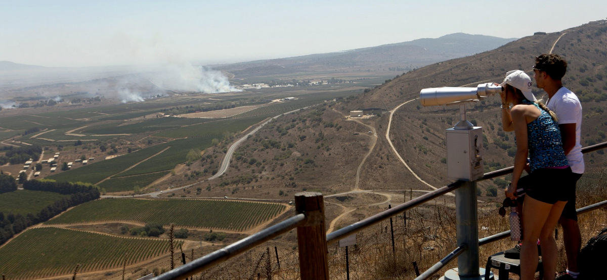 Israeli tourists watch smoke rising near the Syrian-Israeli border as the fighting Syrian army fights to regain control of the Quneitra border crossing from rebel groups. (Atef Safadi/EPA)