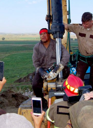A pipeline protester uses PVC pipes to attach himself to a piece of construction equipment along Highway 6 near Bismarck, N.D. (Photo: Phil McKenna/Inside Climate News)