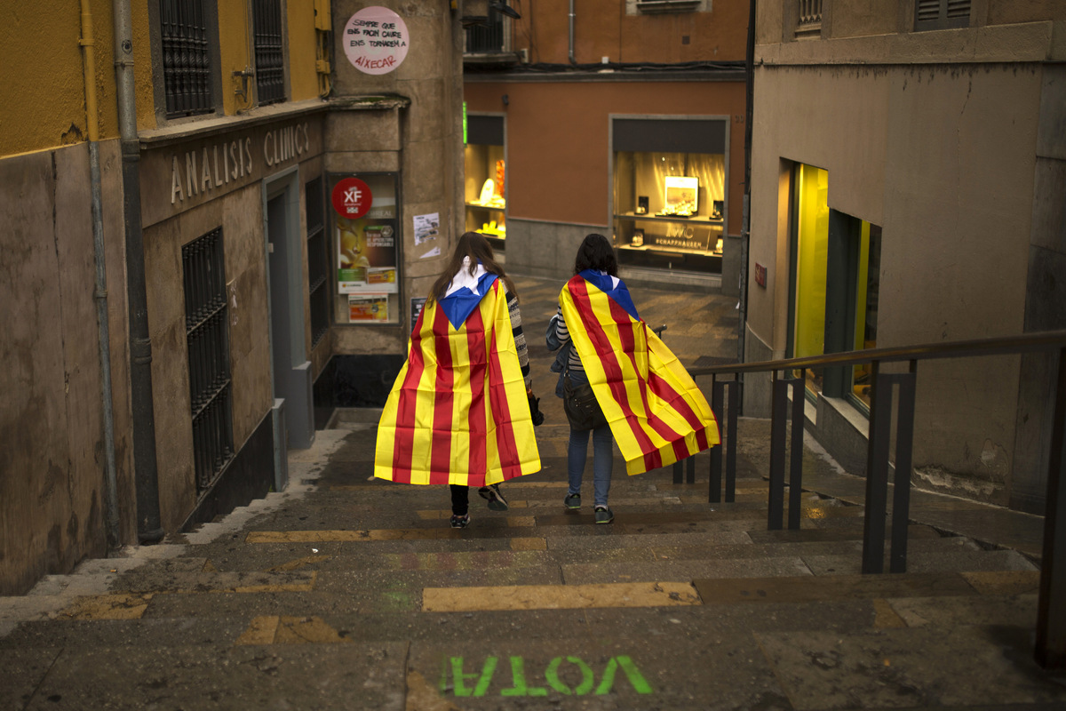 "Women with ""esteladas,"" or Catalonia independence flag, walk along the old quarter in Girona, Spain, Monday, Oct. 2, 2017. (AP/Francisco Seco)"