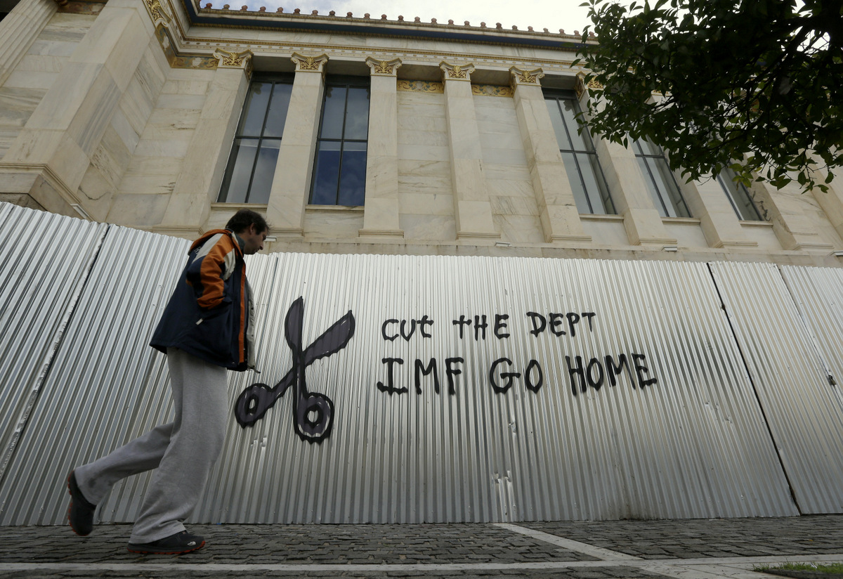 A pedestrian passes anti-austerity graffiti in front of Athens Academy. (AP/Thanassis Stavrakis)