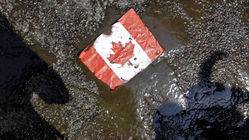 A tattered Canadian flag rests in a soupy, oily mess on the ground.