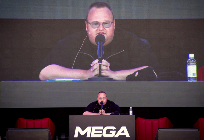 Kim Dotcom with his hands folded on a podium as he speaks into a microphone.