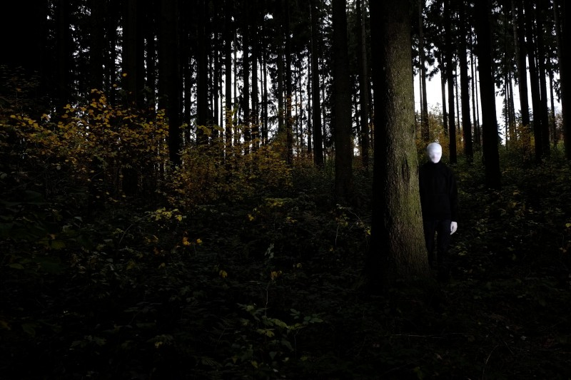 In a deep forest, a humanoid figure dressed all in black but for white gloves & all white featureless face covering, peeks from behind a tree.