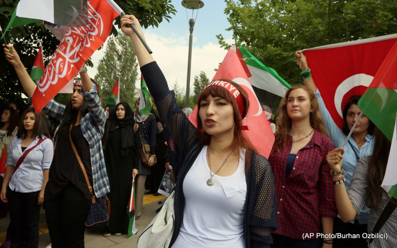 Protesters, many female, with fists raised or holding Palestinian flags.