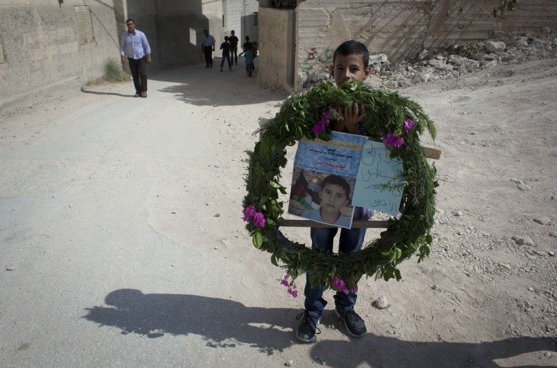 On a dusty street, a young boy carries a wreathe surrounding a memorial poster.