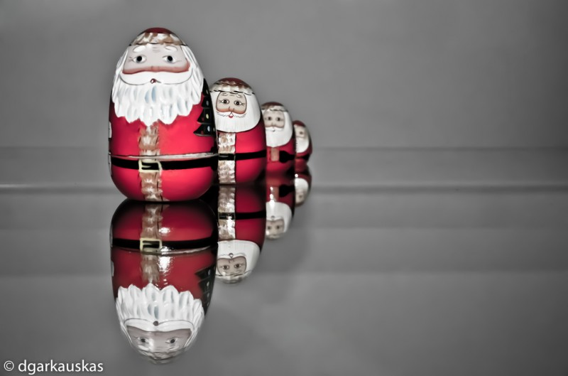 A series of dwindling reflections of a round, cartoonish Santa, as if seen in an infinite mirror.