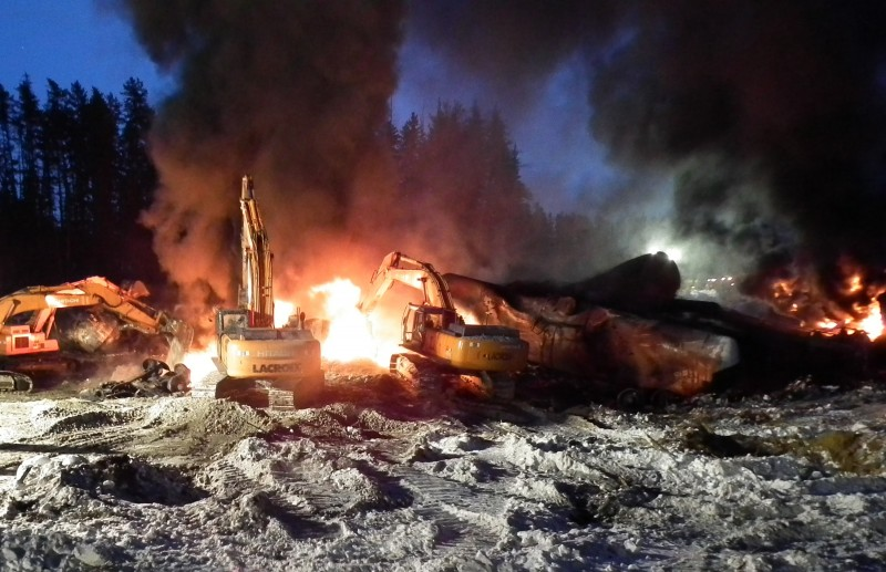 In this Feb. 16, 2015, file photo, provided by the Transportation Safety Board of Canada, workers fight a fire after a crude oil train derailment south of south of Timmins, Ontario. (AP Photo/Transportation Safety Board of Canada, File)