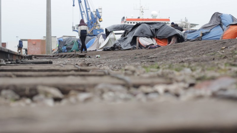 A man past a row of tarp-covered tents on a desolate patch of ground, with the cranes of the Port Of Calais, France visible in the distance. Hundreds of refugees from Syria's civil war ended up in this village while attempting to reach the United Kingdom. (Amel Guettatfi)