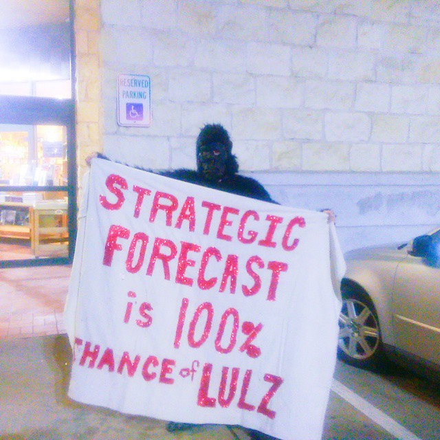 "An ""Anonymous gorilla"" (a protester in a gorilla suit) stood outside Book People in Austin, Texas on February 2, 2015 during George Friedman's book signing. The gorilla's banner reads Strategi Forecast Is 100% Chance Of Lulz. (Kit O'Connell)"
