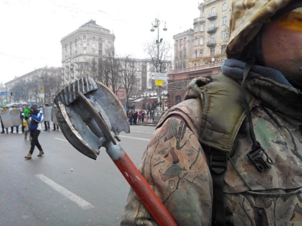 A protester in army fatigues holds a mace, while others with shields stand in the distance. Violent 'Maidan' protests led to a coup in Ukraine in late 2013. (Mstyslav Chernov)