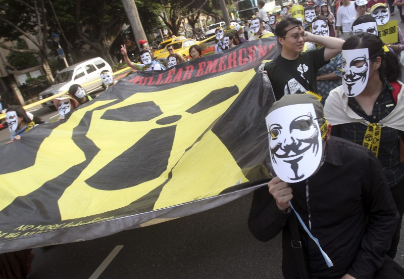 """Protesters carry a large banner bearing a nuclear symbol modified to look like Edvard Munch's """"The Scream"""" during an anti-nuclear demonstration in Taipei, Taiwan Saturday, March 14, 2015. Tens of thousands of Taiwanese took to the streets and demanded the government to scrap its nuclear energy usage. Taiwan's opposition party has long opposed nuclear power, and public caution over nuclear safety has risen following the 2011 nuclear disaster in Japan. (AP Photo/Chiang Ying-ying)"""
