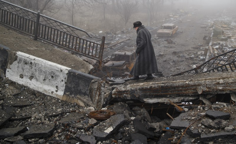 In this Sunday, March 1, 2015, file photo an elderly woman walks across a destroyed bridge, which has collapsed over the road to the airport, the scene of heavy fighting, in Donetsk, Ukraine. Is the media ignoring or even condoning ethnic cleansing by Ukrainian forces?  (AP Photo/Vadim Ghirda, File)