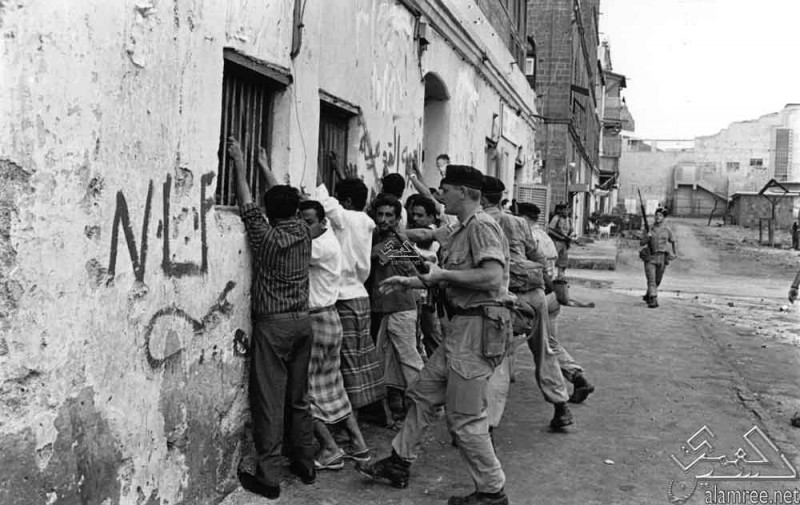 British counterinsurgency forces hold a group of Yemenis against a wall at gunpoint, 1967. The current conflict with the Houthis descends from a long history of British imperialism in the region. (Public domain image by العمري / Wikimedia Commons).