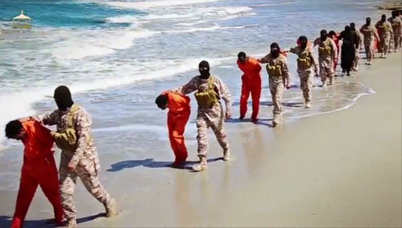 This undated image made from a video released by Islamic State militants, Sunday, April 19, 2015, shows a group of captured Ethiopian Christians taken to a beach before they were killed by Islamic State militants, in Libya.  The New York Times has condemned atrocities like this one while ignoring war crimes by the US and its allies. (Militant video via AP)