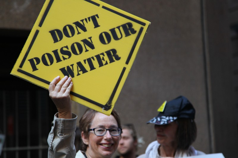"An activist holds a sign, designed to look like a roadside caution sign, that reads ""DON'T POISON OUR WATER"" at an anti-fracking protest in Sydney, Australia on October 23, 2014. New data shows that U.S. fracking is wasting millions of gallons water, even as drought worsens in many parts of the country. (Flickr / Kate Ausburn)"