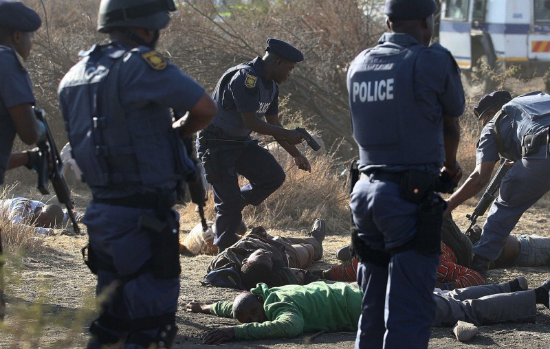 In this file photo taken Thursday, Aug. 16, 2012 police surround the bodies of striking miners after opening fire on a crowd at the Lonmin Platinum Mine near Rustenburg, South Africa. In a report read by president Jacob Zuma, Thursday, June 25, 2015 he said several steps should be taken to step up police work in situations such as those that occurred during the strike on the platinum belt in August 2012, which left at least 44 people dead. (AP Photo-File)