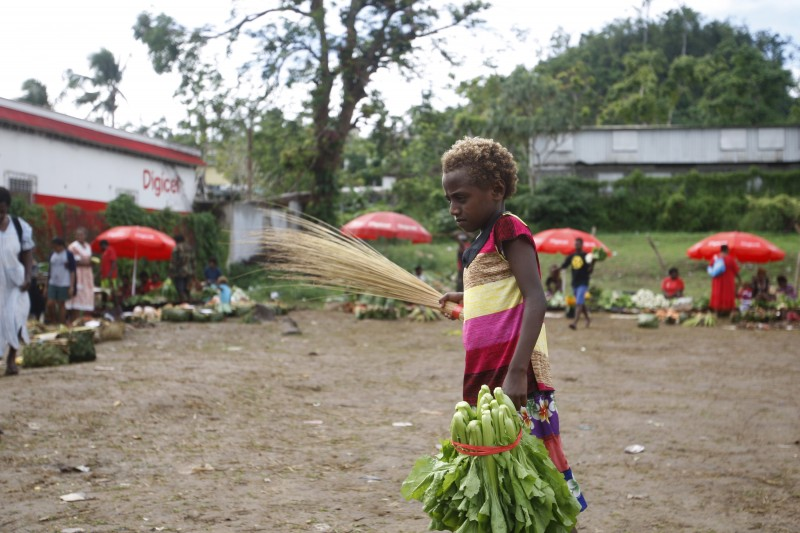 In this Saturday, May 30, 2015, photo, a girl carries goods at an outdoor market in Port Vila, Vanuatu. Many people in Vanuatu believe the nation is suffering the effects of climate change, including changes to crop seasons. (AP Photo/Nick Perry)