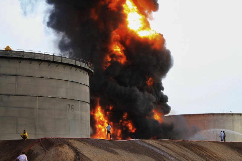 Firefighters work at the storage tanks of an oil refinery following rocket attacks by Shiite rebels, known as Houthis, in the port city of Aden, Yemen, on Tuesday, July 14, 2015. Yemeni forces battling the Shiite rebels in the country's south said they took control on Tuesday of the airport in the strategic port city of Aden, driving the rebels there into the part of the city jutting out into the sea. (AP Photo/Abo Muhammed)