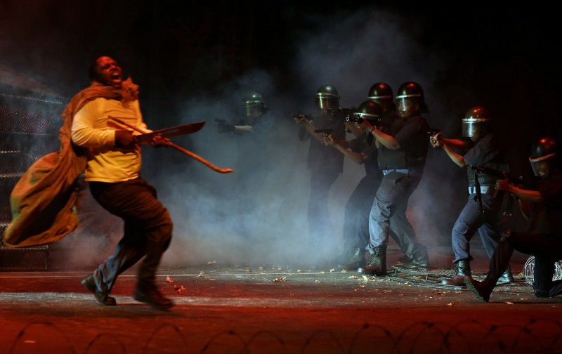 """In this photo taken Thursday, Aug. 13, 2015 actors, re-enact the scene when police, right, open fire on striking platinum mineworkers, in the musical """"Marikana"""" in Pretoria, South Africa.  South Africans sing and dance when they mourn, which is why a musical is a fitting way to commemorate the police shootings of striking miners three years ago, says the lead actor of """"Marikana - The Musical.""""  On Aug. 16 2012, a weekslong labor dispute reached a bloody climax as police opened fire and killed 34 miners in Marikana, a mining town in the North West province. Mavuso Magabane plays the leader of the strike who was killed in the shootings that were the largest loss of life in a police operation since South Africa achieved majority rule in 1994. (AP Photo/Themba Hadebe)"""