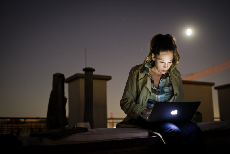 A woman types on an Apple laptop while sitting on a rooftop, her face lit only by the screen and the ambient moonlight. (Flickr / dawolf-)