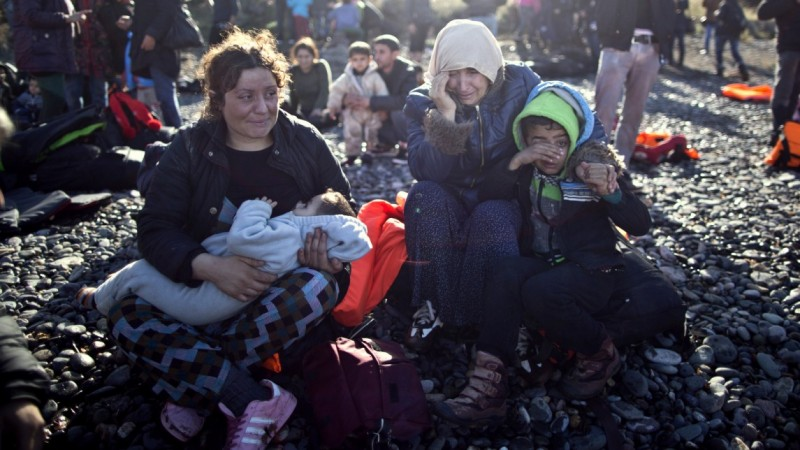 A Yazidi refugee family from Iraq cries while resting on the seashore shortly after arriving on a vessel from the Turkish coast to the northeastern Greek island of Lesbos, Thursday, Nov. 26, 2015. About 5,000 migrants are reaching Europe each day along the so-called Balkan migrant route, stoking tensions among the countries along the migrant corridor including Greece, Macedonia, Serbia, Croatia and Slovenia. (AP Photo/Muhammed Muheisen)