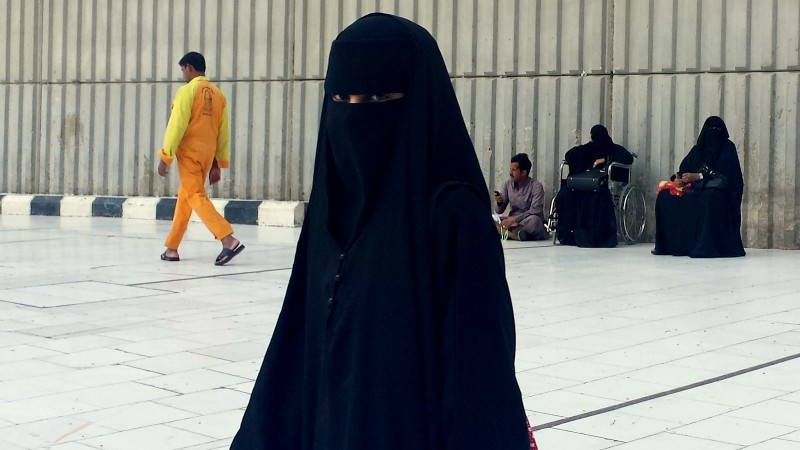 A veiled woman walking in Mecca, Saudi Arabia, where society is governed by a mix of ancient customs and conservative interpretations of Islam. Most women cover their face and by law must wear long flowing black abayas in public. (AP Photo/Aya Batrawy)